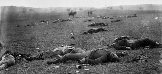 "Brady associate Timothy O'Sullivan aptly subtitled this photograph of slain Union soldiers at Gettysburg ""A Harvest of Death."" The men's shoes have been removed by always needy Confederates."