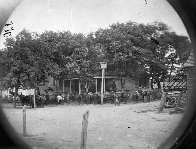 Union cavalry horses are tethered around the Old Church Hotel near Cold Harbor, Virginia, which functioned as Maj. Gen. Phil Sheridan's headquarters during the run-up to Trevilian Station.
