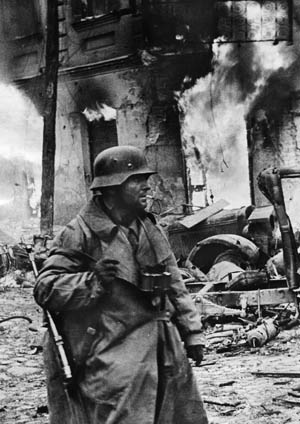 The strain of combat evident on his face, a German panzergrenadier in Zhytomyr, Ukraine, appears oblivious to the destruction around him. This photo was taken on December 21, 1943.