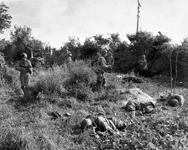 American paratroopers near Carentan search for a German sniper who killed their fellow soldiers in the foreground. The bocage of the Cotentin Peninsula, with its dense borders of woodland, afforded the Germans excellent defensive positions.