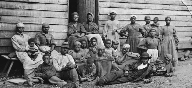 "A large group of ""contraband"" slaves rests at a plantation near Pamunkey Run, Virginia, after escaping captivity."