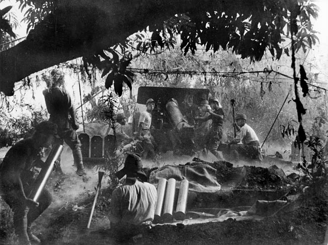 A Japanese artillery crew blasts American or Filipino positions during jungle fighting on Bataan.