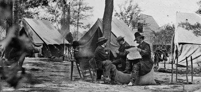 Maj. Gen. Ambrose Burnside, reading a newspaper, sits beside Mathew Brady, left, at Burnside's IX Corps headquarters at Cold Harbor, Virginia, in the summer of 1864.