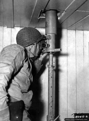 An American soldier peers through a bunker periscope at Batterie Grandcamp-Maisy after its capture.