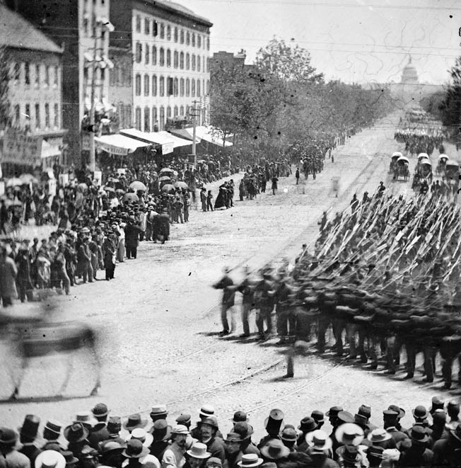 Infantry from XX Corps in Maj. Gen. John W. Slocum's Army of Georgia wheels onto 15th Street in front of Mathew Brady's well-aimed camera. Ambulances can be seen in the background.
