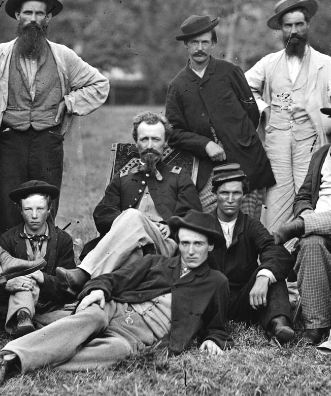 Sergeant Milton W. Cline (seated) disguised himself as a Confederate scout and reported on the location of 125 Confederate military camps and other installations during a harrowing mission behind enemy lines in winter 1863.
