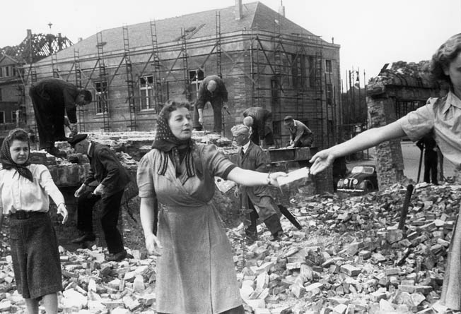 Despite widespread destruction, Hamburg citizens pitch in to clean up the damage as best they can. With most men serving in the military, women did much of the clean-up after bombings.