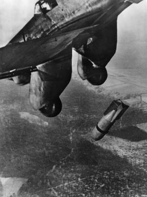 "A Junkers Ju-87 ""Stuka"" releases its bomb on enemy positions. The Stuka dive bomber was considered ""airborne artillery"" in support of lightly armed paratrooper forces."