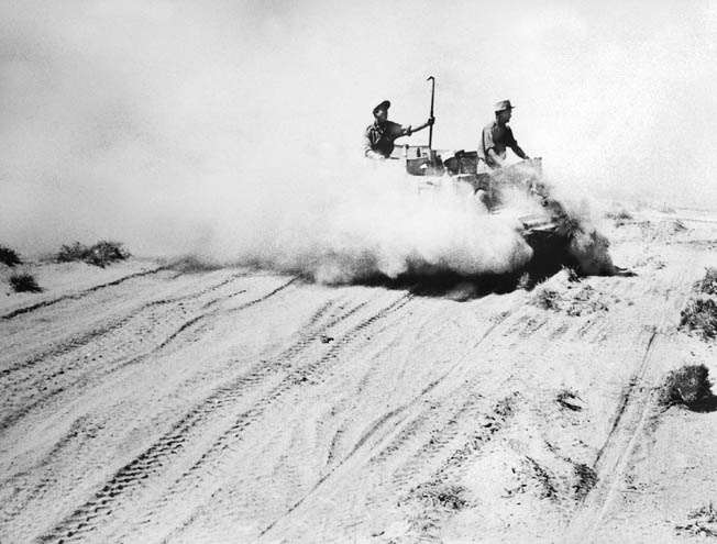 Free French soldiers of the heroic 13th Demi-Brigade of the Foreign Legion drive an armored vehicle across a dusty stretch of the North African desert during the battle at Bir Hakiem. These soldiers bought precious time for the withdrawal of British Commonwealth troops to El Alamein.