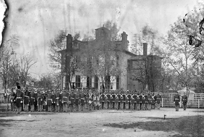 A well turned out battalion of Marines parades past the Commandant's House in Washington in 1864. Band members are pictured at left, with drummer boys in the center.