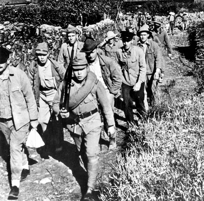 In this photograph, apparently staged for Japanese propaganda purposes, a group of seemingly healthy and well-treated Allied prisoners of war is led along a mountain trail toward a worksite near its camp. During their conquest of much of the Pacific, the Japanese captured hundreds of thousands of prisoners and were overwhelmed by the numbers. Cultural differences and an inability to cope with the burden led to widespread atrocities.