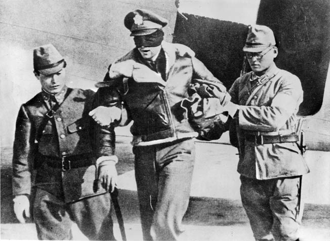 Japanese guards transport blindfolded Lieutenant Robert L. Hite, co-pilot of Plane 16, to a POW camp in China. The pilot, Lieutenant William Farrow, was executed by the Japanese.