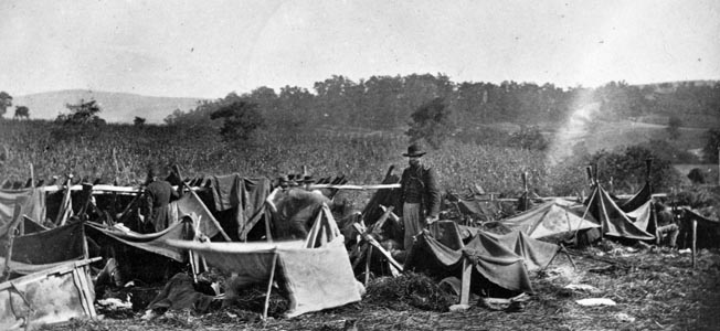 A Union doctor from the 14th Indiana Volunteers tends to Confederate wounded after the Battle of Antietam in September 1862. Blankets stretched over fence railings were the only protection from the elements at this crude medical aid shelter.
