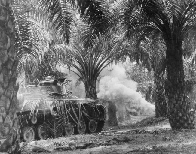 In this photo taken in January 1942, a Japanese Type 97 Chi-Ha light tank fires at American and Filipino positions in a grove of palm trees. The Type 97 tank was inferior to contemporary American designs; however, these tanks were still effective against troop concentrations and contributed to the Japanese conquest of the Philippines.