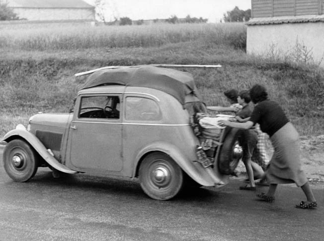 The former occupants of an automobile push the vehicle along a road somewhere in France after it has run out of gas. The roads from Paris into the French countryside were clogged with refugees fleeing the onrushing Germans, who invaded their country on May 10, 1940.