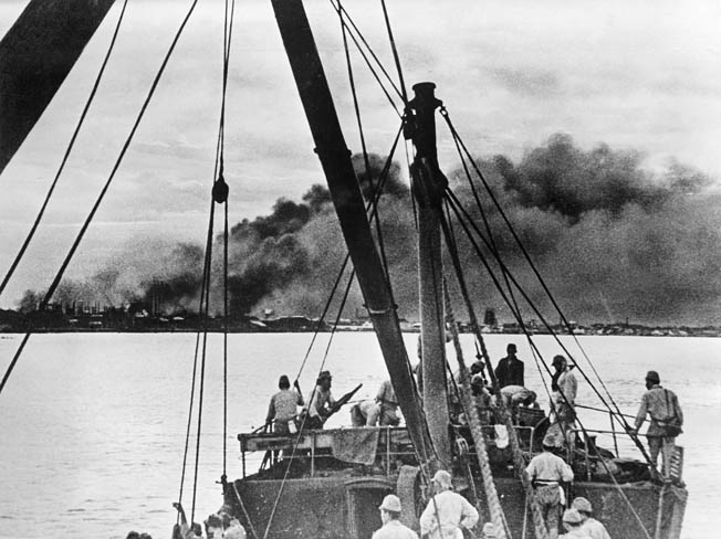 Additional Japanese troops landed by sea during the invasion of Sumatra in February 1942. In this photo Japanese soldiers approach the Sumatran coast as oil fields but in the distance.