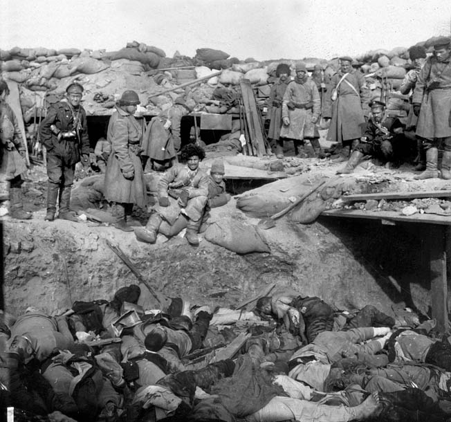 "Russian defenders loom over a trench filled with dead Japanese soldiers. The ""banzai spirit"" cost the Japanese greatly."
