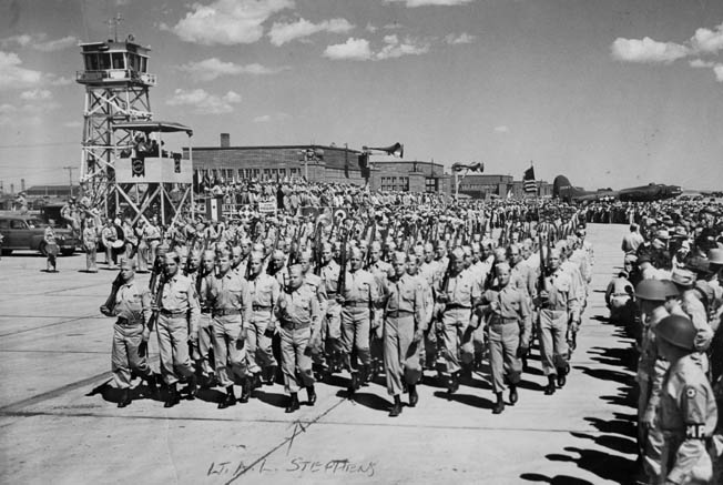 First Lieutenant Albert L. Stephens (left of center) leads Headquarters Company, 3rd Battalion, 507th Parachute Infantry Regiment, 82nd Airborne Division, on August 23, 1943, during grand opening festivities of the Alliance Army Airfield, Alliance, Nebraska. Most of the men in this photograph fought at Graignes.