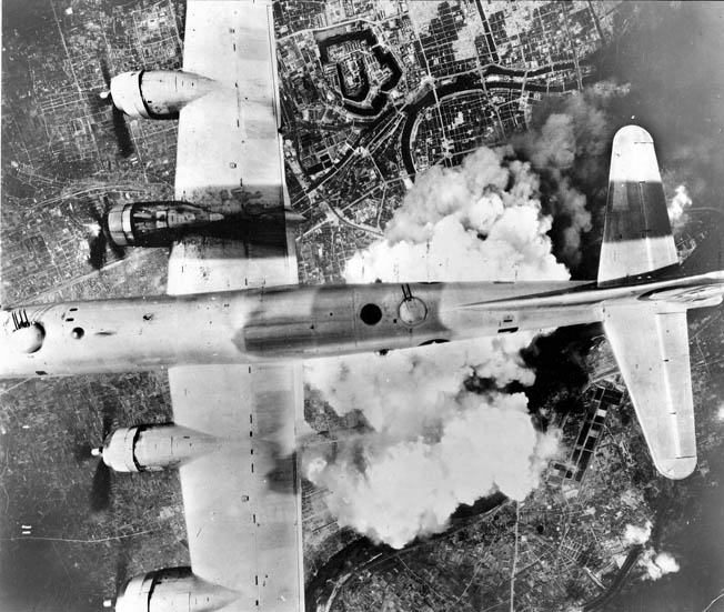 With smoke and dust rising below, a B-29 bomber flies over Osaka in June 1945.