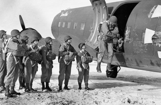 Medical personnel assigned to the 1st SSF practice parachuting from the door of a parked C-47 in Helena, Montana. The unit was trained for airborne and mountain operations in all types of weather.