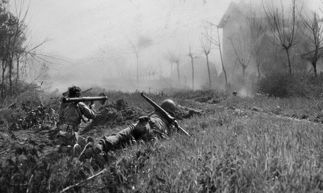 A 1st SSF man armed with a bazooka (3.5-inch rocket launcher) fires at a farmhouse near Anzio where German snipers are holed up.
