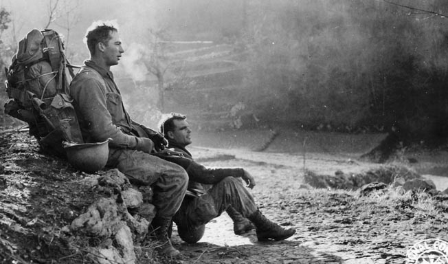 A heavily laden Force man and his buddy take a break during a march near Cevaro, east of Cassino, January 1944. Within a month they would be fighting at Anzio.
