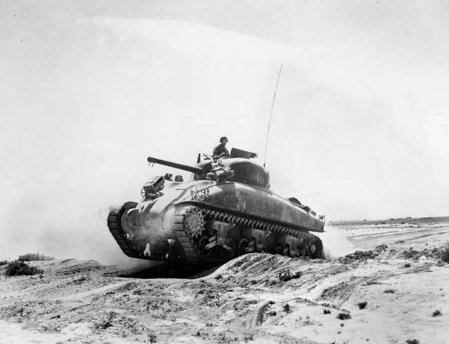 An M4 Sherman tank rumbles over a sand dune in the Tunisian desert. Bromberg faced off against a German tank for the first time during the drive across the desert in 1943.
