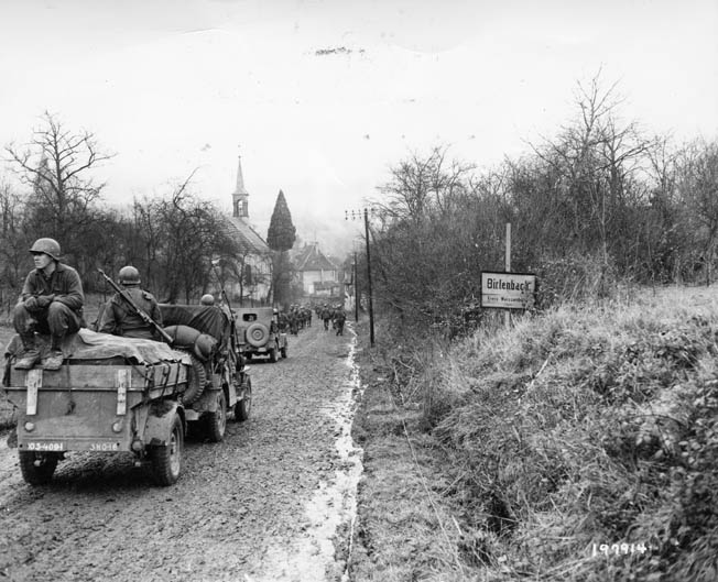 On December 14, 1944, two days before the opening of the Battle of the Bulge, infantrymen of the 103rd Division ride atop jeeps and trailers as they move into the town of Birlenbach, France. The 103rd crossed into Germany the following day and began its assault on the Siegfried Line.