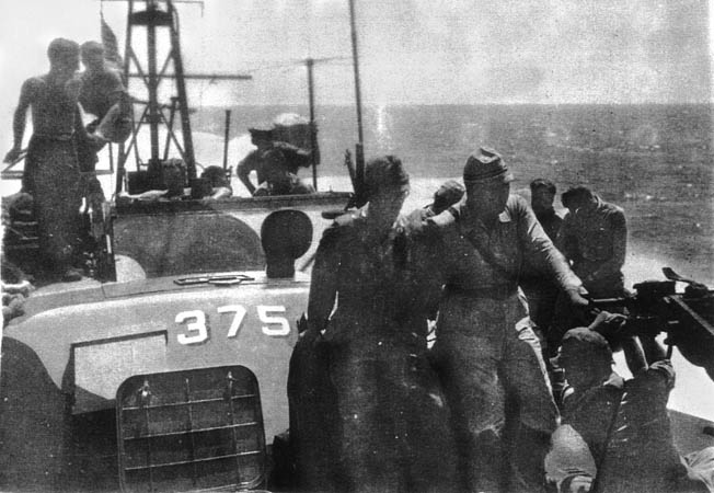 """With Hank Blake at the wheel in PT-375's cockpit, the Japanese surrender delegation (foreground) is treated to a """"rough ride"""" in choppy seas, bracing themselves with the gun mount and ready box, September 8, 1945."""