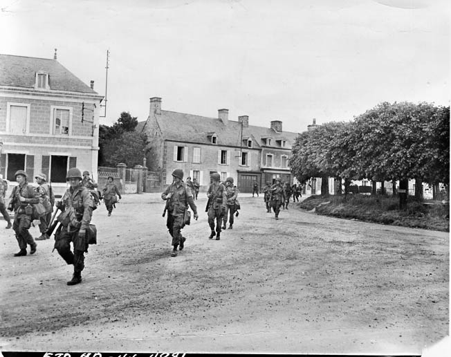 Men of the 101st Airborne march through Ste. Marie-du-Mont on their way south Carentan.