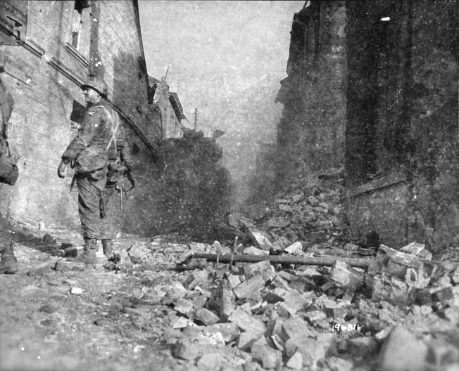 Inside the embattled town of Geilenkirchen on November 19, 1944, two American soldiers and a British tank move warily through the rubble of destroyed buildings.