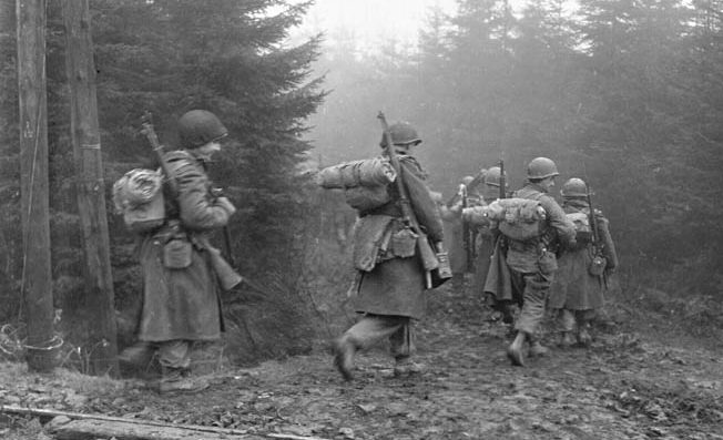 Men of the 325th Glider Regiment, 82nd Airborne, move into the woods in heavy fog during operations in Western Europe.