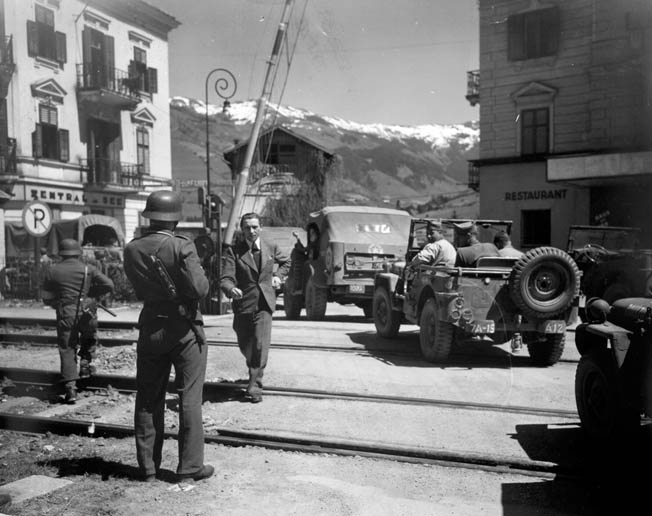 GIs in a convoy pass armed Germans providing security In Zell-am-See, Austria, just a few weeks after Germany surrendered.