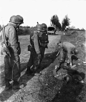 East of the Geilenkirchen salient on November 19,1944, American soldiers of Company B, 334th Regiment, 84th Infantry Division attach a wire to the corpse of a dead German soldier. They dragged the body, which concealed a Teller mine, away from the explosive device it had covered.