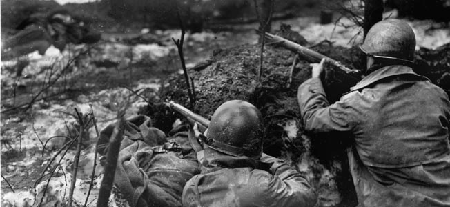 With the body of a dead German soldier lying yards from their position, two men of the 393rd Regiment, 99th Infantry Division scan the distance from their foxhole during the Battle of the Bulge. Sergeant Walter's platoon of the 393rd was trapped behind enemy lines during the great battle in the West in the winter of 1944-45.