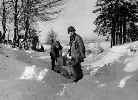 Improvising with a coffin attached to a pair of skis, two soldiers of the 99th Infantry Division bring supplies to a position at Elsenborn. This photo was taken in mid-January 1945, about a month after the Ardennes Offensive began.