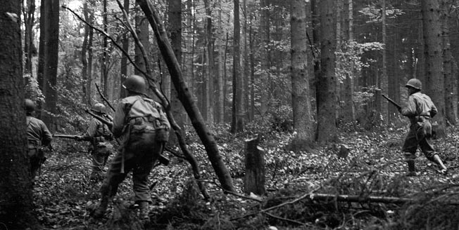 "Soldiers of the U.S. 28th Infantry Division, nicknamed the ""Bucket of Blood"" because of their red keystone shoulder patch that identified them originally as a Pennsylvania National Guard division, advance warily through the dense Hürtgen Forest near the town of Voosenack."