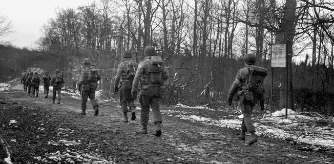 Soldiers of the 2nd Ranger Battalion slog their way along a muddy road on their way to Hill 400, the scene of a fierce stand against repeated German attacks.