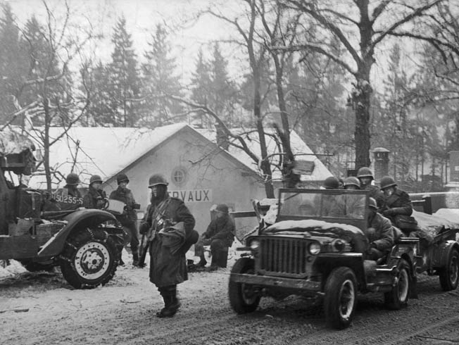 GIs of the 26th Infantry Division move through Clervaux, scene of much hard fighting in northern Luxembourg, after the town's liberation, January 25, 1945.