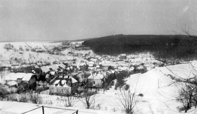 The snow-covered town of Ludweiler, Germany, appears tranquil in the midst of war. This photo was taken from the vantage point of a church overlooking the town on January 8, 1945, from the sector that was occupied by the U.S. 106th Cavalry. German troops defended the wooded area visible at upper right. LEFT: Soldiers of the Seventh Army man a .50-caliber machine gun during the days leading up to Operation Nordwind, the German offensive in southern France. As General George S. Patton, Jr.'s Third Army advanced northward during the Battle of the Bulge, the 106th Cavalry was charged with occupying an area Patton's command had vacated.