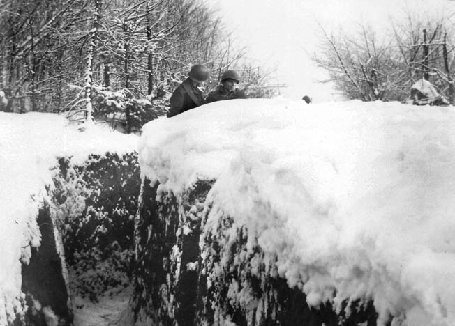 From the cover of a snow bank near Ludweiler, Germany, T/5 Tom Klora and Pfc. Eugene Wimberly chat while on alert in January 1945. The German forces engaged in the Nordwind offensive were so close at times that their dogs could be heard barking when sentries changed, and their conversation was audible.