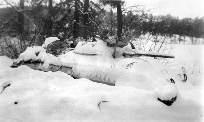 Joseph Pedraza, a T/5 with Troop B, 106th Cavalry Squadron, sits in the turret of a snow-blanketed armored car near Ludweiler, Germany, in January 1945. The armored car has been secreted in a trench dug by the cavalrymen of Troop B to provide better concealment.