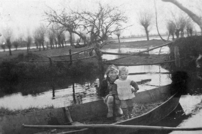 Marthe and Jean Claude Rigault shown in their father's boat, used to retrieve U.S. equipment bundles from the marsh behind them, near Graignes. Like many of the French, the Rigaults risked their lives to aid the Americans.