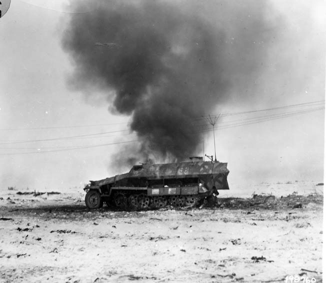 A German half-track burns after being hit. Bromberg's tank crew knocked out a half-track that drove into the 2nd Armored Division's line. Bromberg later ventured over to the destroyed vehicle for a closer look.