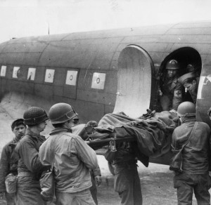 A wounded soldier on a stretcher is being lifted aboard a C-47 for evacuation from France to England.