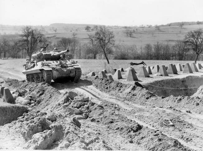 An American tank destroyer  maneuvers through the Dragon's  Teeth of the Siegfried Line at the  German border. The last line of defense included tank traps, pill  boxes, and bunkers. Fighting became more intense east of the border.