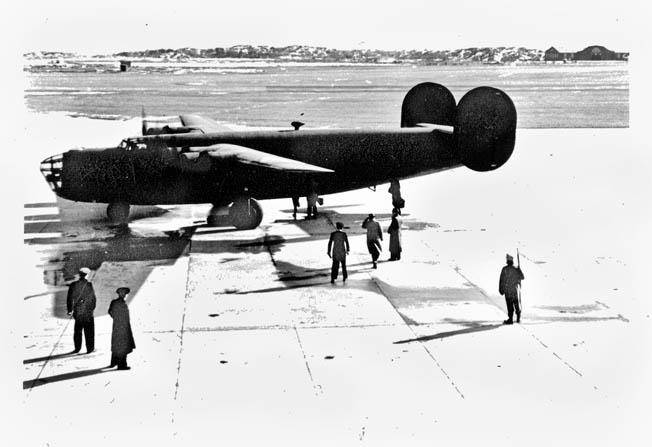 "Prior to its departure with rescued Allied airmen and Norwegian resistance fighters aboard, a ""Sonnie"" B-24 Liberator sits on an airfield at Goteborg, Sweden, while a Swedish soldier stands guard."