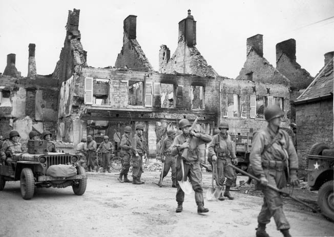 American infantrymen move through a bombed-out French town. While in Caumont, Puhalovich's half-track was strafed by a German plane and blown up.