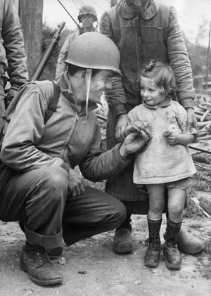 A friendly GI gives a piece of candy to a French girl. Puhalovich also gave candy to a little girl and was thanked with a flower.