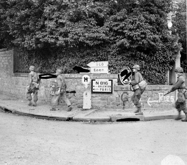 A patrol of 1st Infantry Division soldiers enters an unidentified French town shortly after Allied planes had driven the Germans from it. Note that an Army censor has blocked out information that might provide useful information to the enemy.